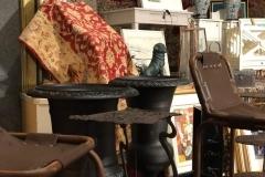 Gjutjärnsurnor, figurer och bord. Barstolar med brun metallstomme och vintageläder.